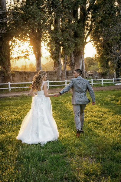 Newly married couple holding hands and running in the field during sunset