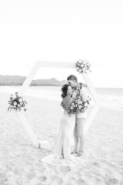 bride and groom kissing on the waimanalo beach