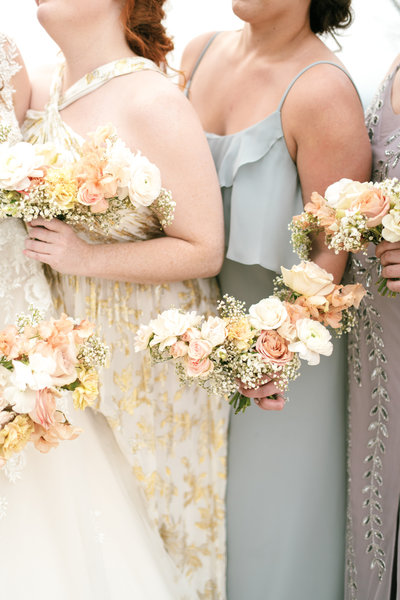 a close up of the bridesmaid holding their pastel color bridesmaid bouquets wearing mismatched bridesmaid dresses