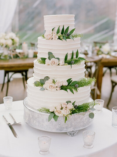 White tiered-wedding cake decorated with small pink flowers and green leaves