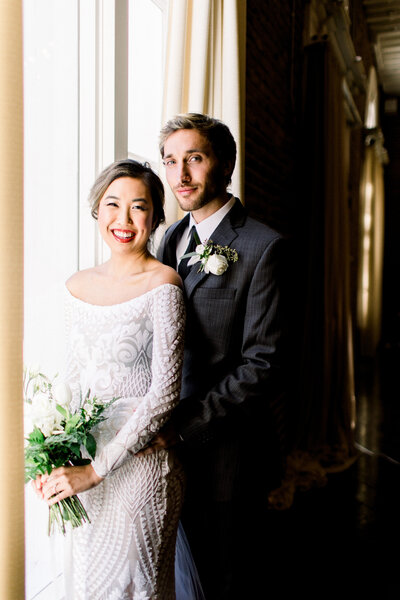 Bride smiling in beaded luxury wedding gown holding a bouquet while groom looks seductively at the camera