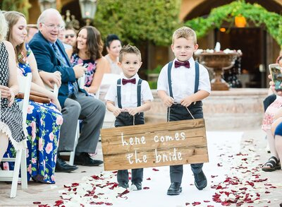 ring-bearer-holding-here-comes-the-bride-sign