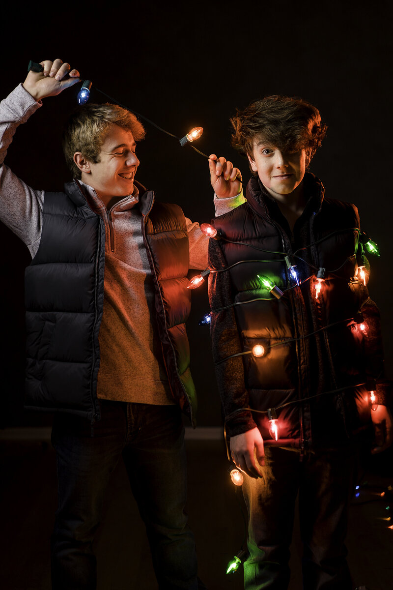 Fun Christmas sessions in Caldwell, NJ teen boy ties his brother up in christmas lights