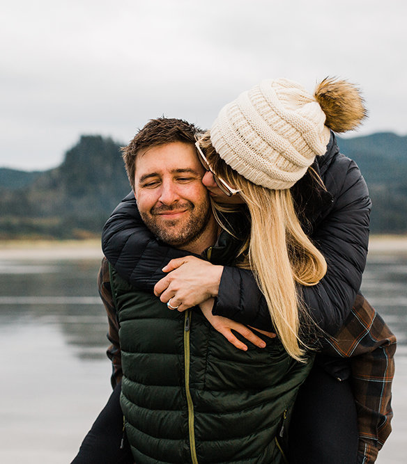 a woman kisses her partner on the cheek during a piggyback ride on the washington coast for their adventure engagement session with amy galbraith