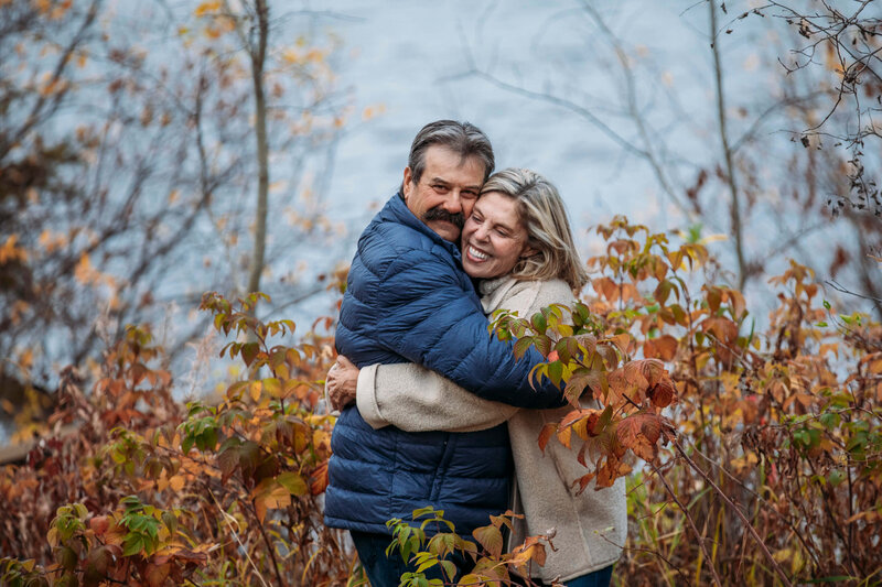 couple hugs and laughs in the fall foliage
