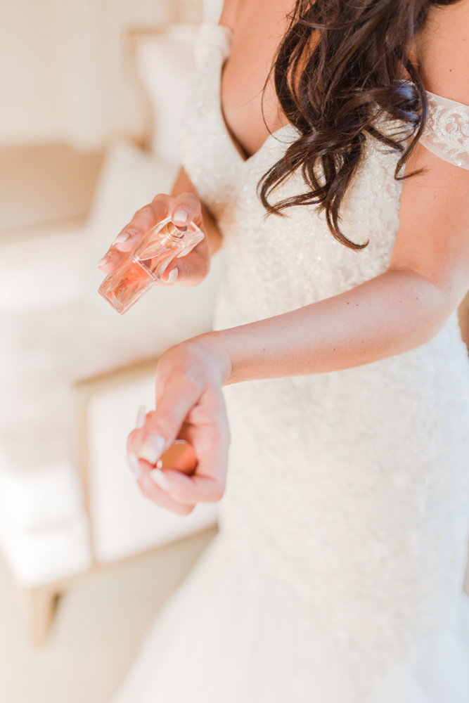 bride putting on perfume at great marsh estate wedding in northern virginia by costola photography