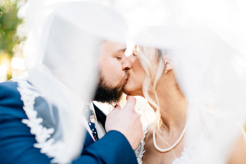 bride and groom kiss under bride's veil