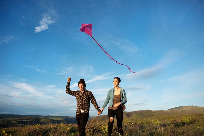a man and woman fly a kite while running through the grass