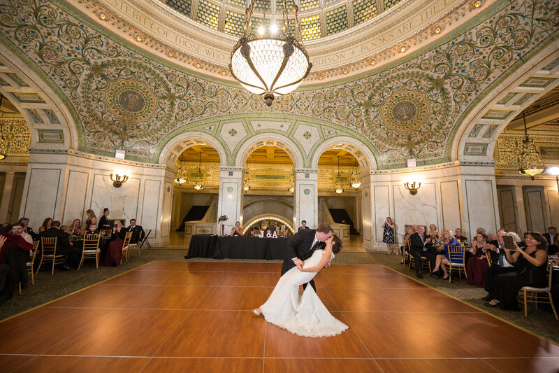 Bride and groom kiss at their wedding reception in Preston Bradley Hall at the Chicago Cultural Center.