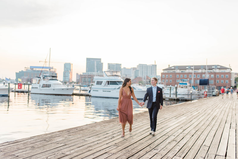 Couple walking hand in hand on boardwalk in Fells Point, Baltimore