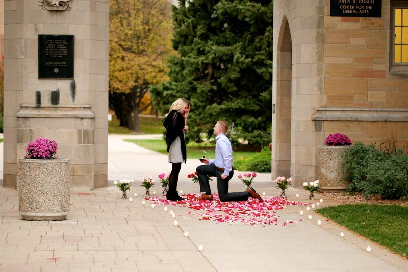 Man proposing to girl in front of arches