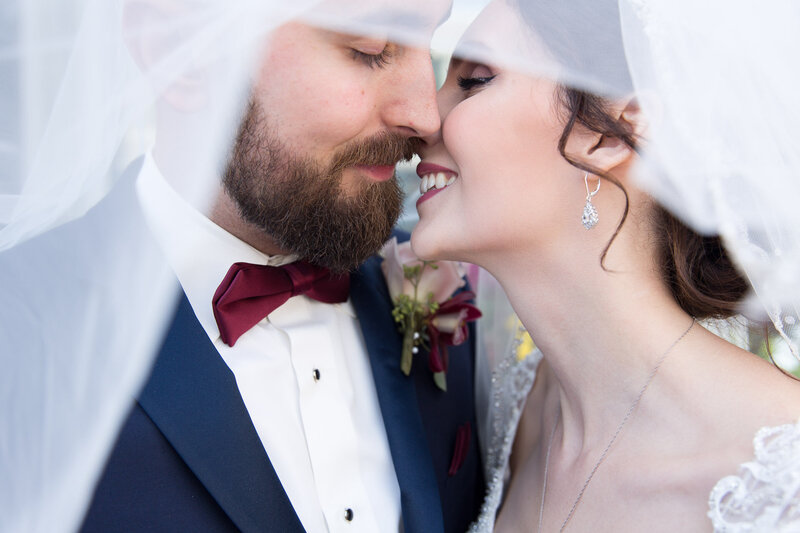 bride and groom kissing under veil on wedding day in port huron