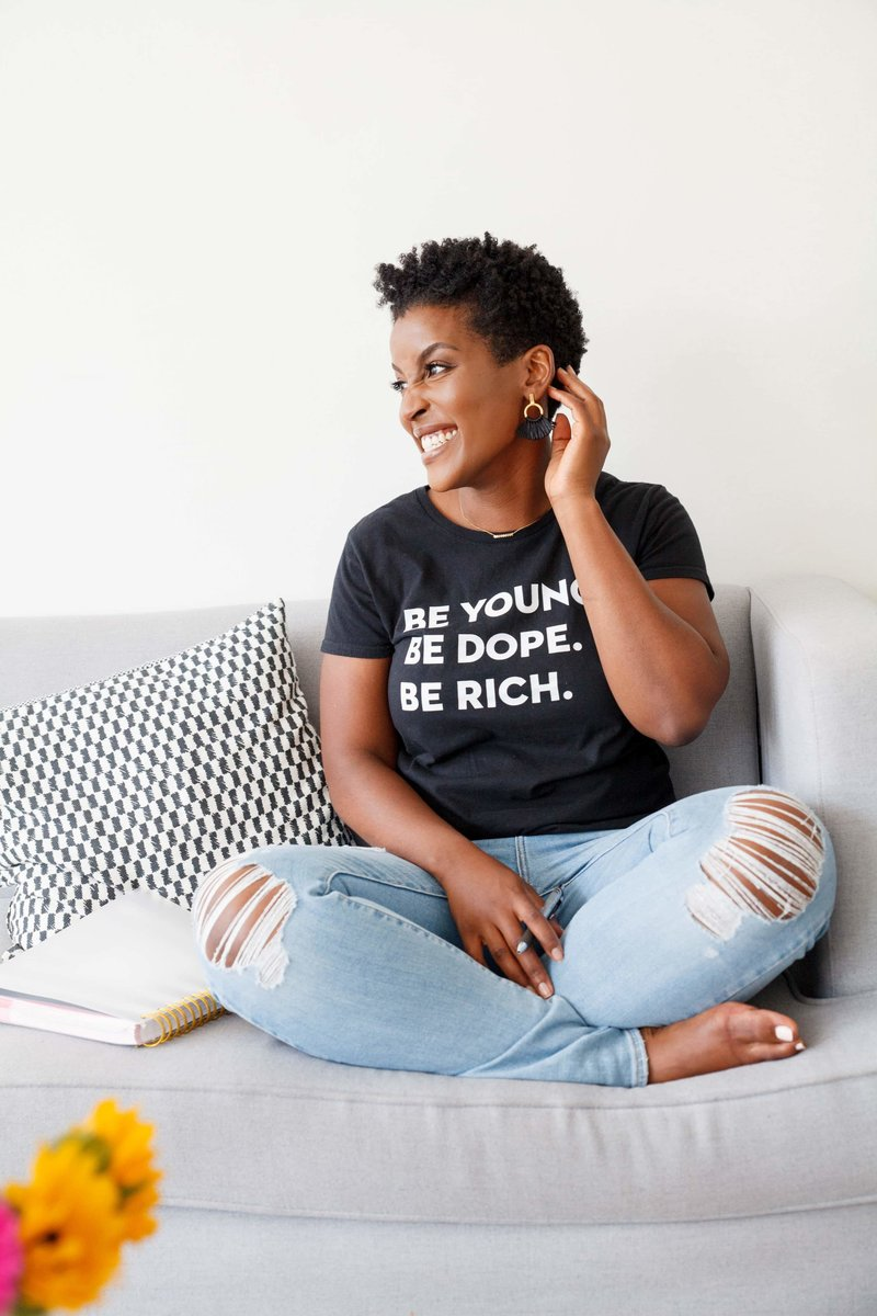 Woman with short curly black hair sitting with corssed legs in a gray couch wearing a black shirt that reads Be young Be dopeBe rich
