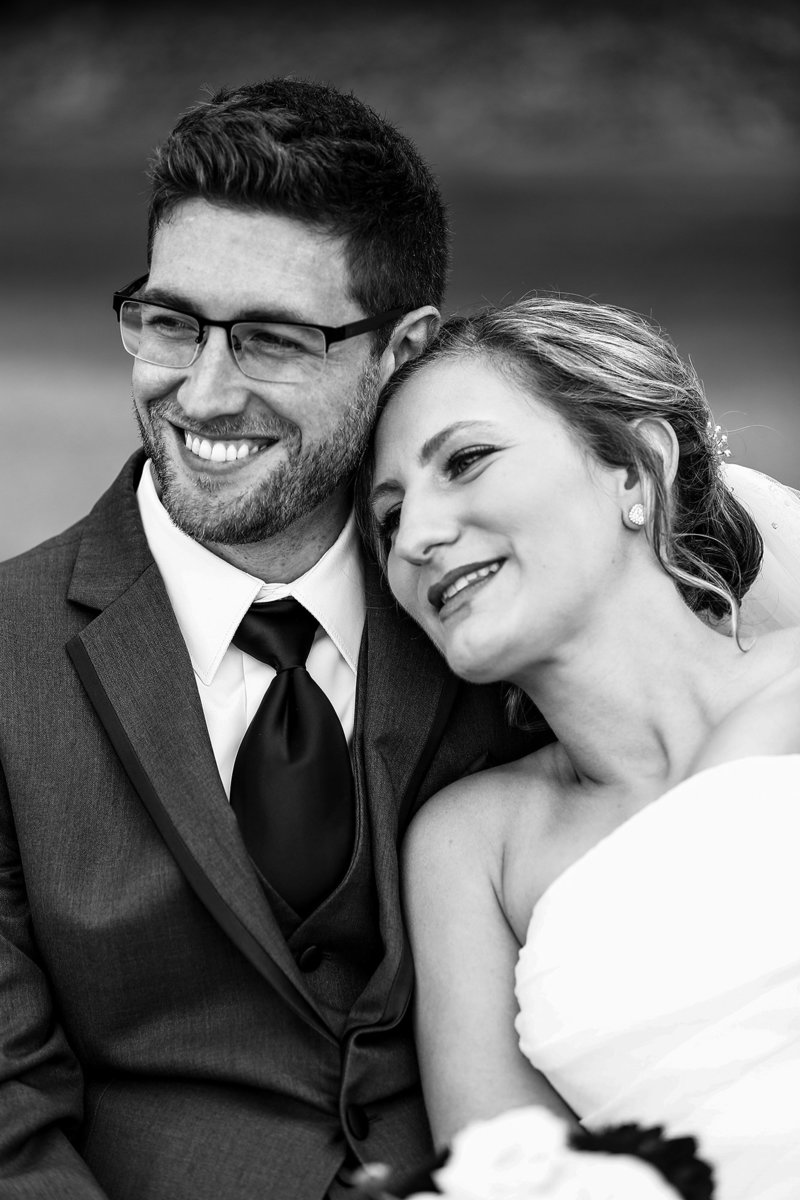 bride leans on smiling groom's shoulder as they look off into the distance