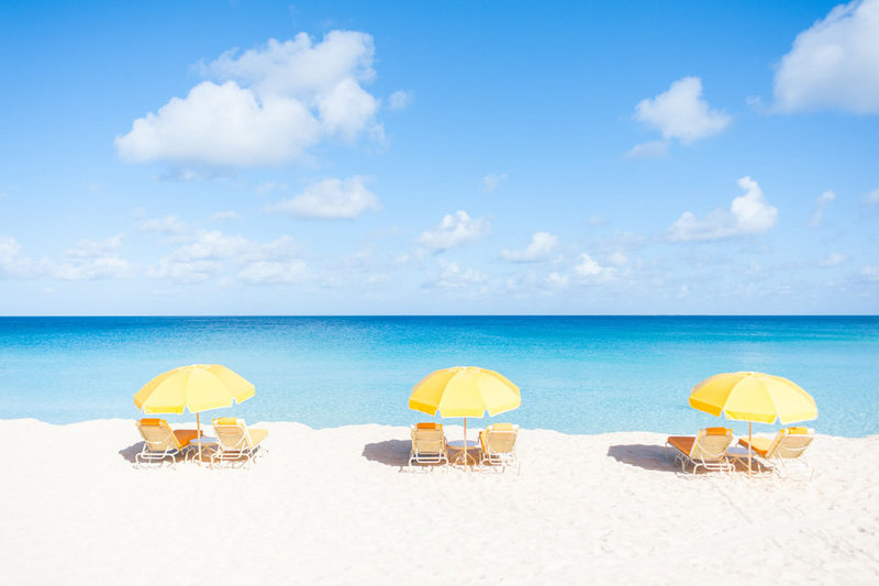 three yellow beach umbrellas at malliouhana's mead's bay in anguilla