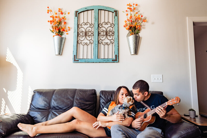 During an at-home engagement photo session a couple sits on their couch with their dog while the man plays a guitar