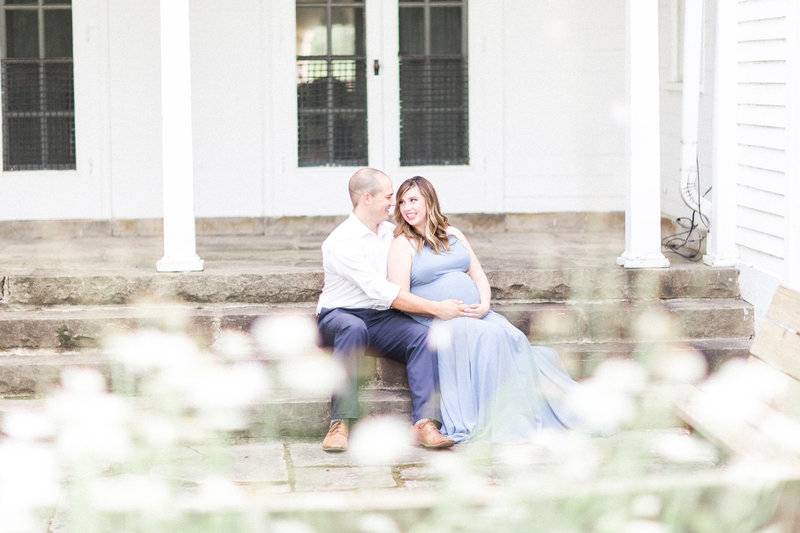 Couple sits on stairs with wild flowers during session with Cleveland Maternity Photographer at Quail Hollow Park