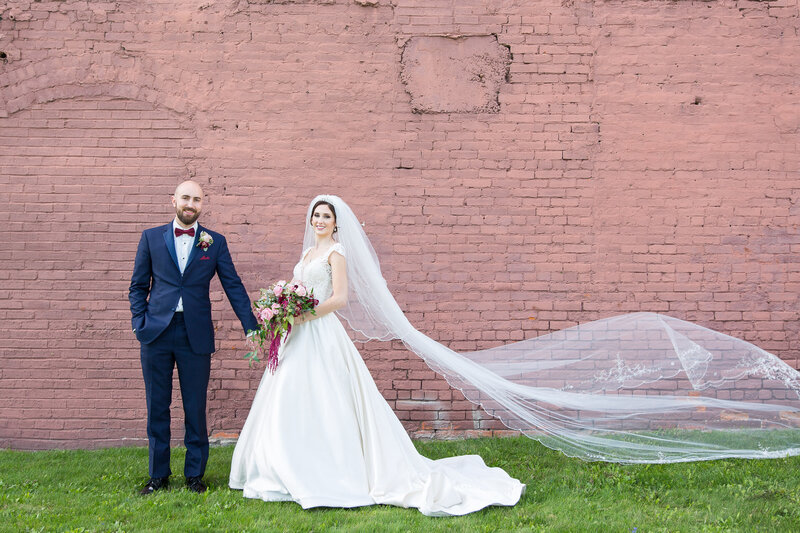 bride and groom portrait with flowing veil at pink wall in downtown port huron