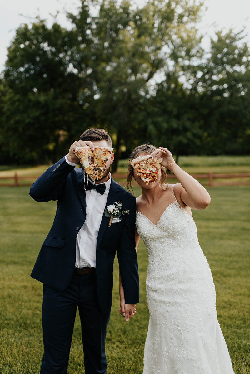 Bride and Groom holding pizza in front off their faces during their wedding day