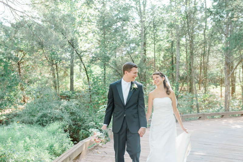 Bride and groom walk hand in hand in the forest