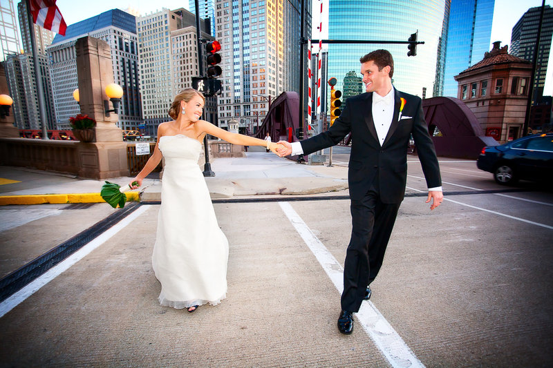 Bride and groom walking hand in hand  in downtown Chicago with sky scrappers in the backgrounds.