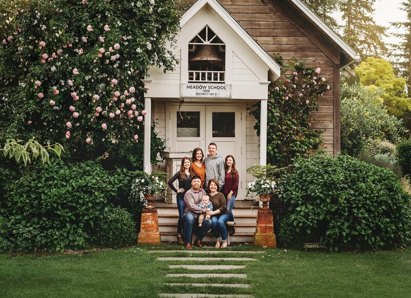 Family sits on the front steps of their home for family portrait
