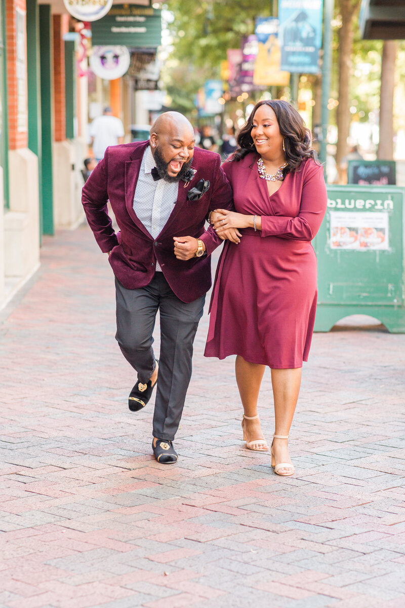 bride and groom laughing with each other as they walk through downtown memphis at their engagement session