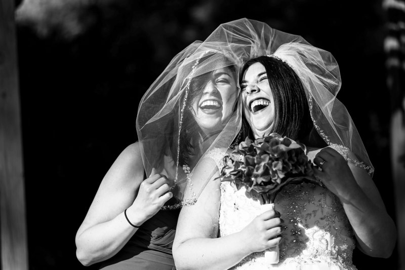 Bride laughs with her sister at St. Mary's Catholic Church wedding