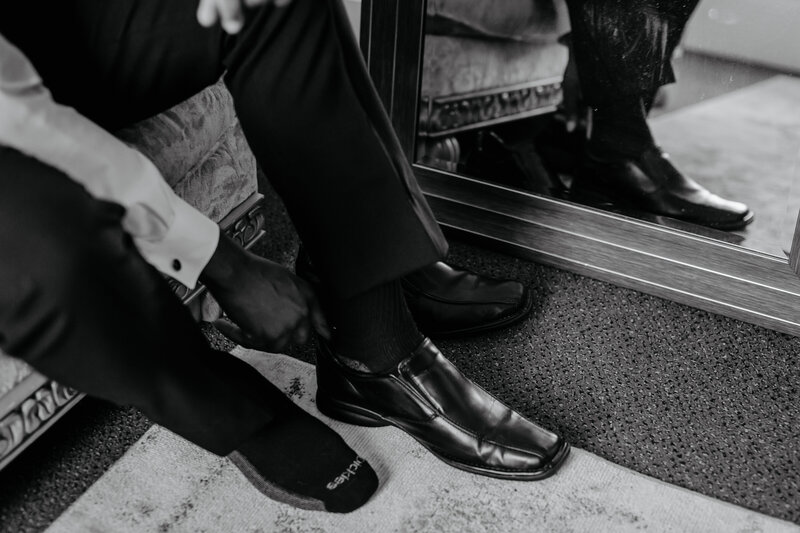 "alt=""groom putting on shoes for wedding day"""