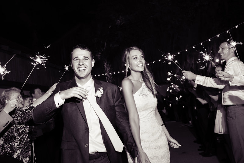 a bride and groom exit their wedding reception surrounded by sparklers