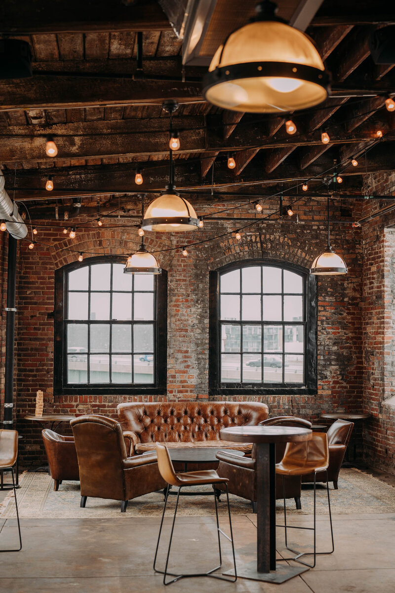 the 4th floor cocktail lab has brick walls cafe lights wooden ceilings and a beautiful view of the ben franklin bridge in philadelphia distilling company shot by philadelphia wedding photographer alex medvick