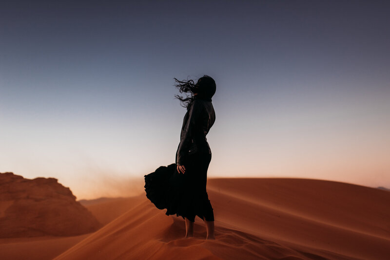 woman in black standing on a red sand dune with the wind blowing her dress and hair