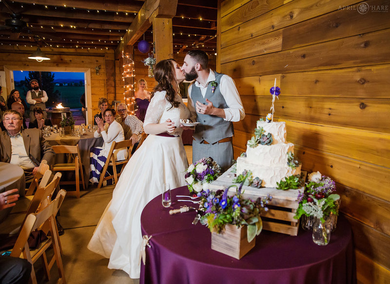 Cake cutting inside the barn at rustic Denver wedding Chatfield Farms