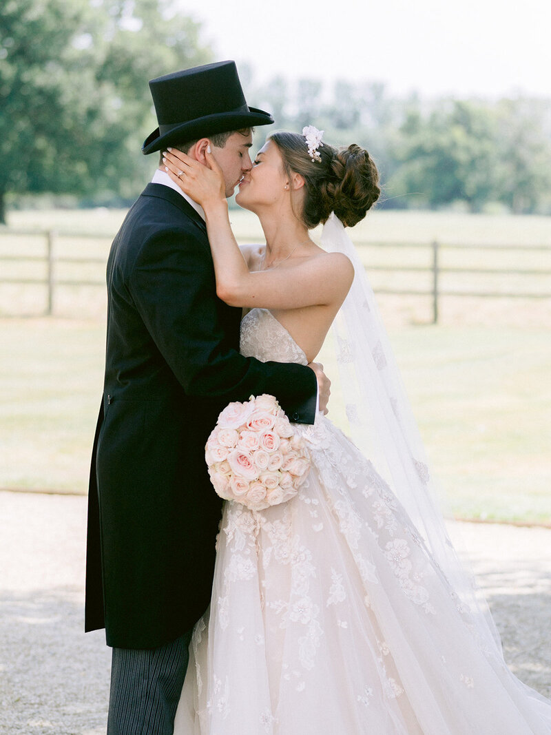 Bride and Groom kiss outside Eastington Park regency style wedding venue