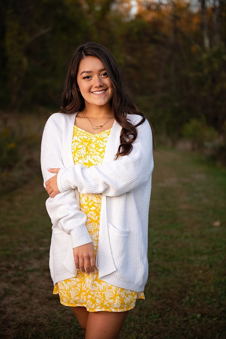 High school senior girl in yellow floral dress and white cardigan standing holding her arm in grassy field at Round Hill Park in Elizabeth, PA