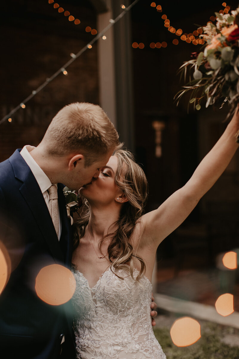 Gorgeous bride lifts up wedding bouquet as she kisses her groom. Beautiful blurred out lights in front of them. Taken by The Creative Des Moines Iowa Photographer