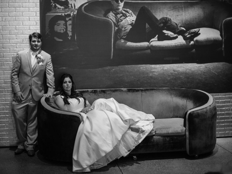 Bride and groom pose for a portrait in the couch at their Andy Warhol Museum wedding reception