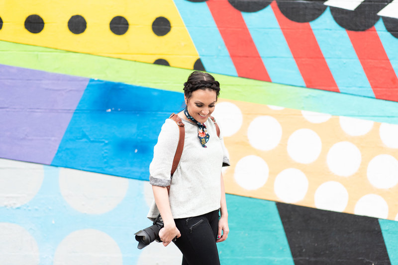 Woman wearing dual camera straps and standing in front of a colorful mural in the Gulch of Nashville