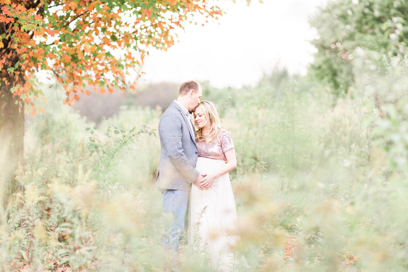 Pregnant couple embrace during field maternity session with Cleveland maternity photographer