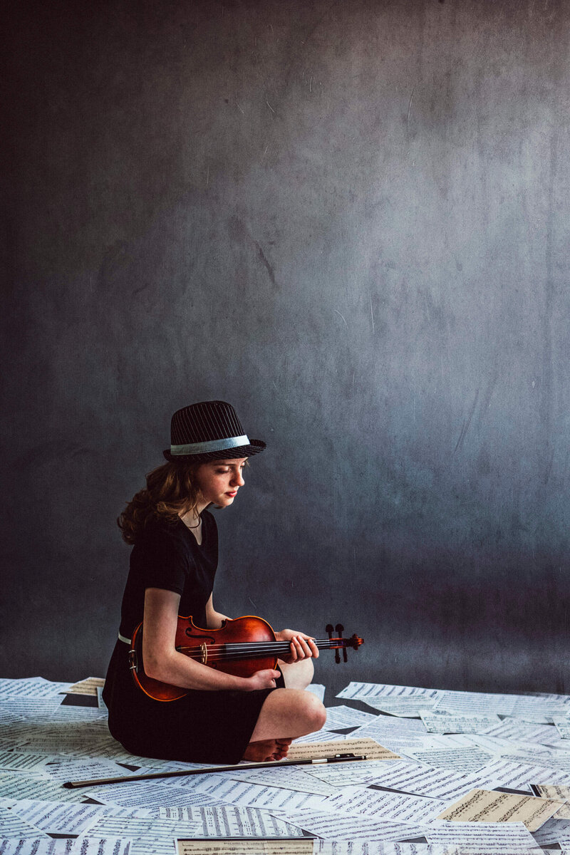 girl sits on sheets of music holding violin