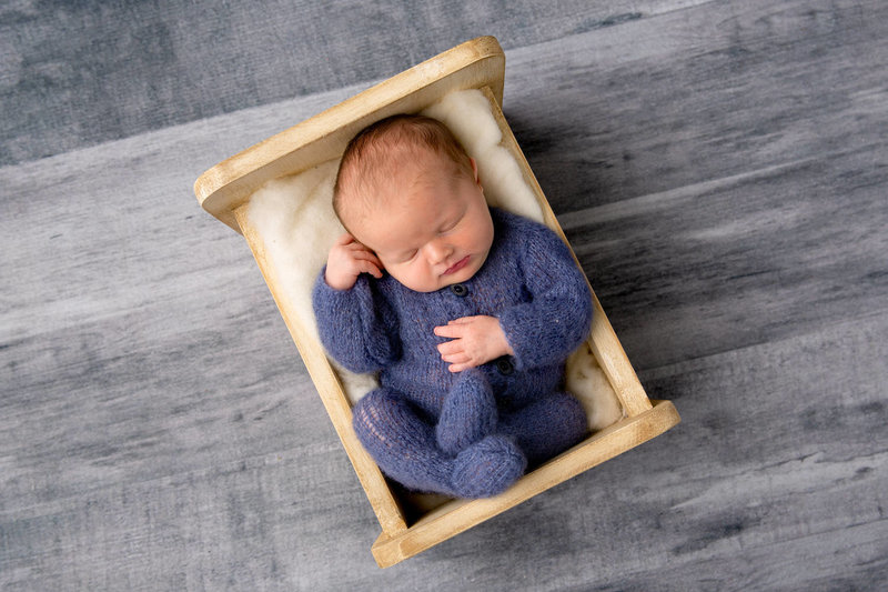 Newborn boy dressed in blue in a cradle on a grey background