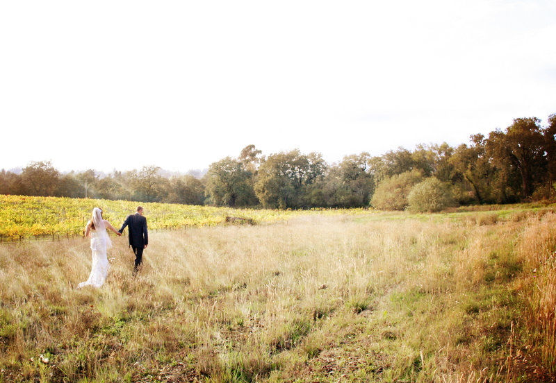 bride and groom walking in a field, wine country weddings