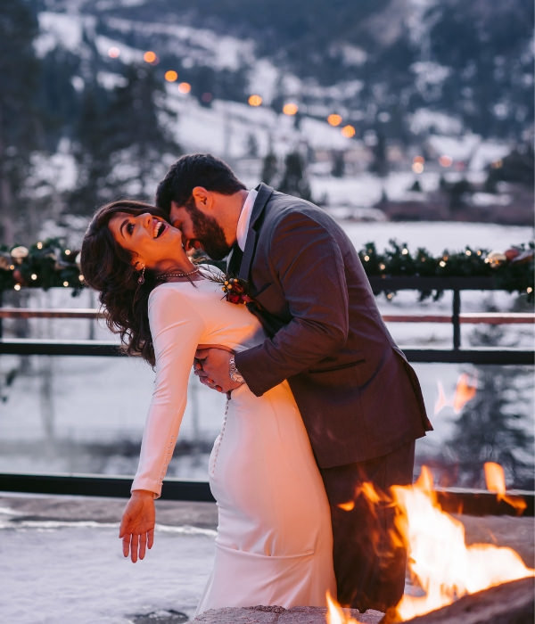 Joyful Lake Tahoe Wedding Planners couple on balcony in snow by firepit, winter wedding at venue The Resort at Squaw Creek, Lake Tahoe, Joy of Life Events home page image by Charleston Churchill