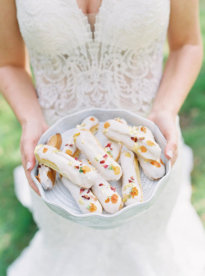 Bride holding pastries in a bowl up to the camera