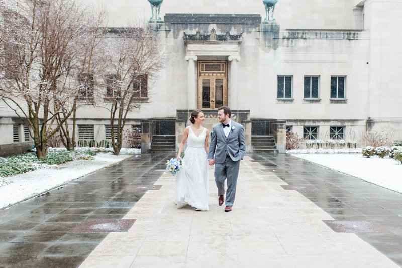 Bride and groom hold hands and walk in the snow in the courtyard at the Cincinnati Art Museum