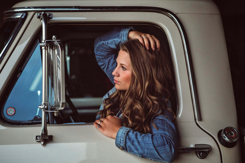 girl looking in mirror of vintage Ford truck