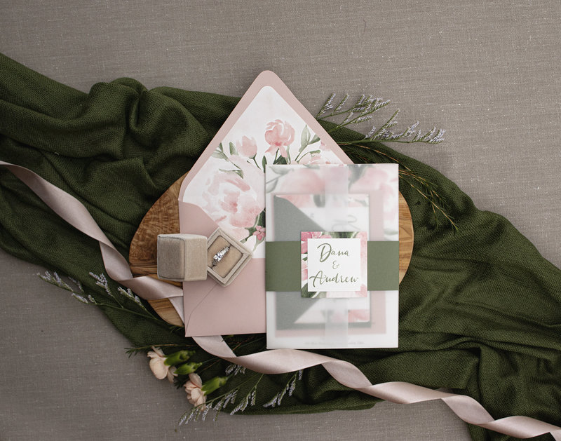Peony watercolor invitation shown with a beautiful vellum wrap, belly-band with double layered emblem and a gorgeous floral envelope liner by Brittney Nichole Designs.