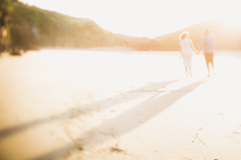 an out of focus photo of a couple walking on Piha Beach, New Zealand