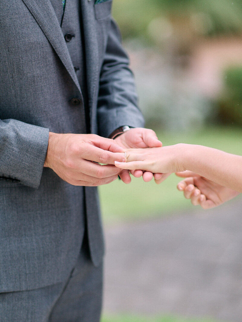 Closeup of groom putting ring on brides finger