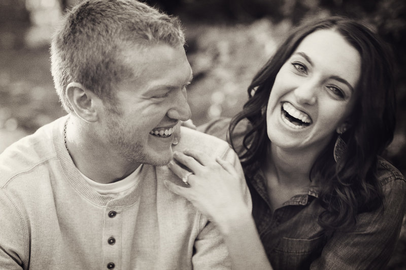 Black and white photo of engaged couple laughing.